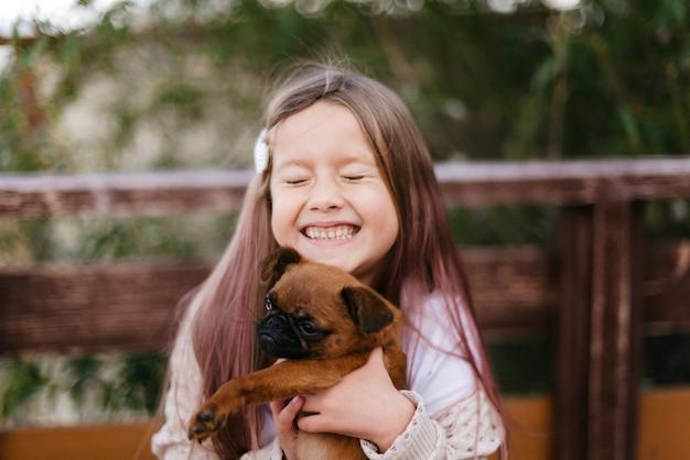 그녀의 팔에 작은 갈색 개를 들고 웃는 어린 소녀
