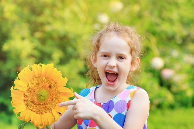 Laughing little girl holds sunflower.