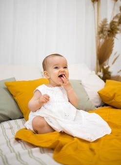 白い綿のドレスを着て笑っている少女がベッドに座っている