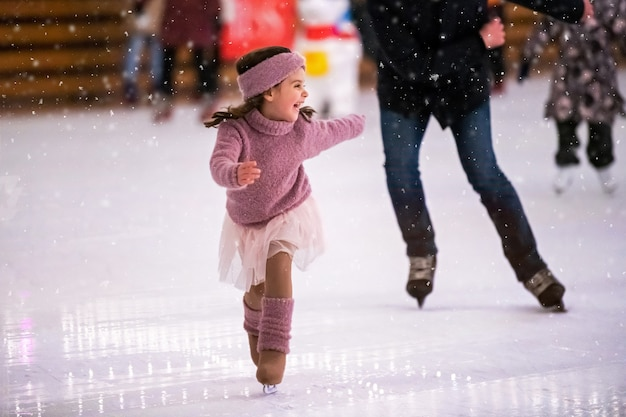 Laughing little girl in a pink sweater is skating on a winter evening on an outdoor ice rink, it is snowing