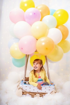 Laughing little girl sits in basket decorative balloonnd looking away.