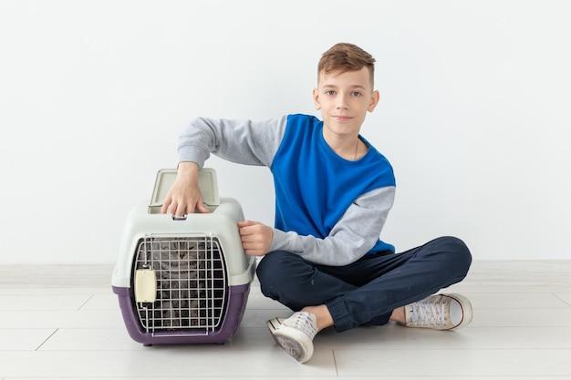 笑っている小さなポジティブな男の子は、床に座っている彼の隣にスコティッシュフォールドの猫と一緒にケージを持っています