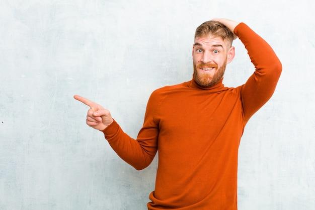 웃고, 행복하고, 긍정적이며 놀랍게 보이고, 측면 복사 공간을 가리키는 훌륭한 아이디어를 실현