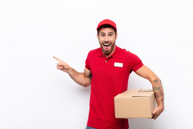 Laughing, looking happy, positive and surprised, realizing a great idea pointing to lateral copy space. delivery concept