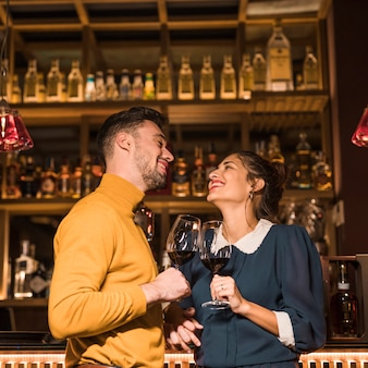 Laughing man clanging glasses of wine with smiling woman