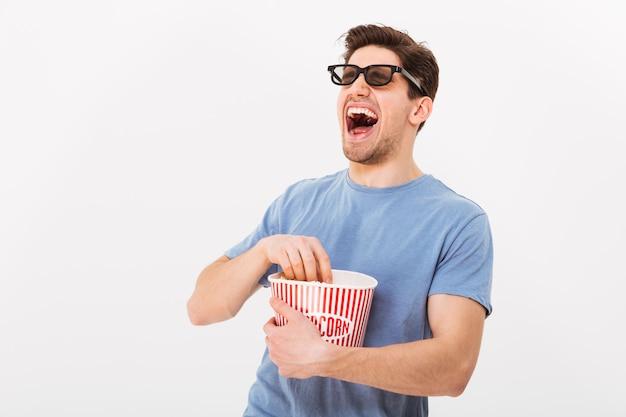 Смеющийся человек в футболке и 3d-очках ест попкорн из ведра и смотрит через серую стену