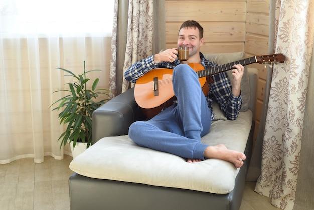 Смеющийся человек играет на гитаре и пьет кофе