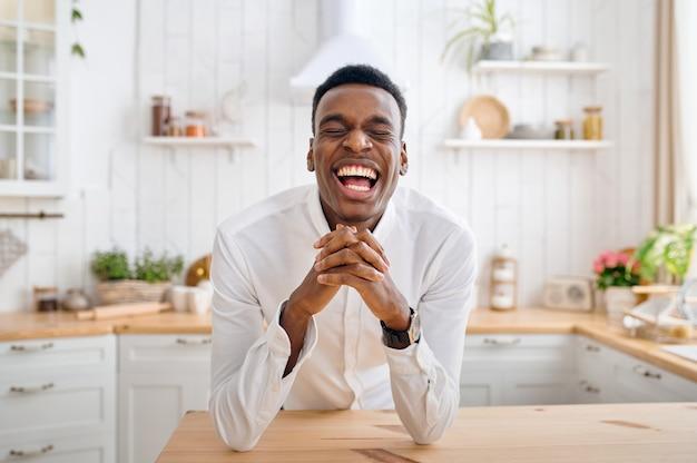 キッチンのカウンターに座っている笑う男。陽気な男性が朝、自宅のテーブルでポーズをとる、幸せなライフスタイル