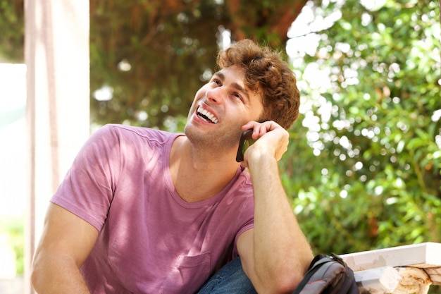 Laughing man sitting with backpack and cellphone in park