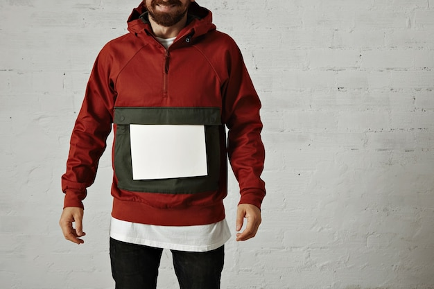 A laughing man in a stylish red and grey anorak with a plain white sheet of paper on his large front pocket on white