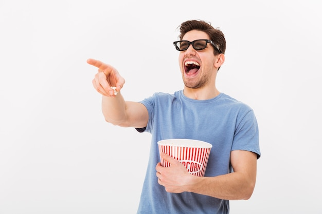 Laughing man in t-shirt and 3d glasses holding bucket with popcorn while pointing and looking away over grey wall