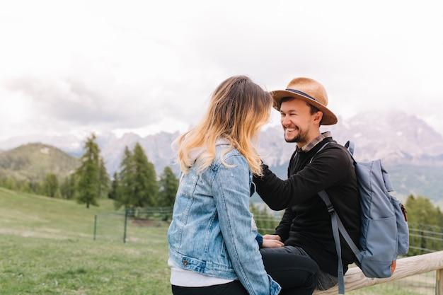 山のフィールドに座っている彼の金髪のガールフレンドを見ている青いバックパックで笑う男