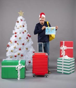 Смеющийся человек с красным чемоданом держит карту обеими руками на сером изолированном