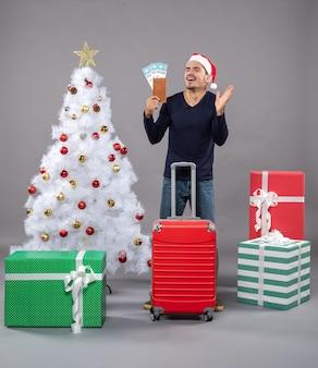 Uomo che ride con la valigia rossa che mostra i suoi biglietti di viaggio e il cinque su grigio