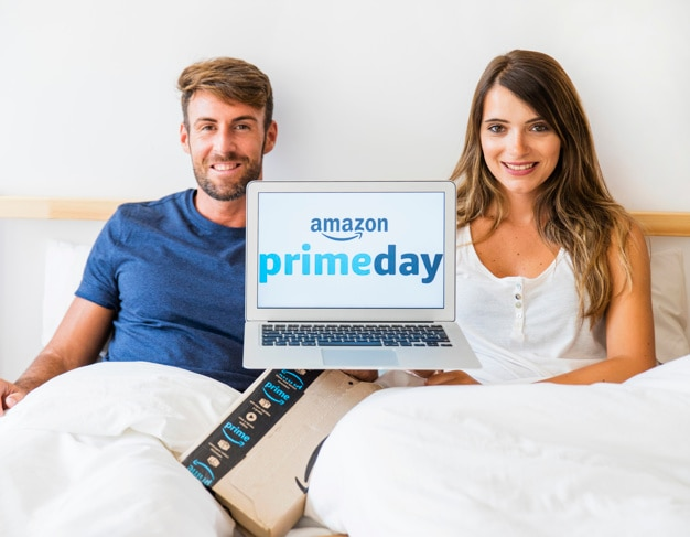 Laughing man and woman in bed with laptop