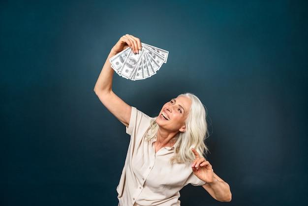 Смеется зрелая старуха, держа в руках деньги.