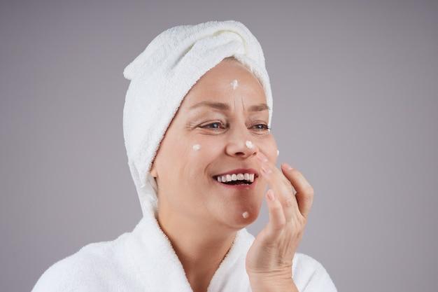 彼女の顔にクリームを適用し、彼女の頭に白いタオルで成熟した女性を笑う。フェイシャルケアのコンセプト。灰色の壁に隔離