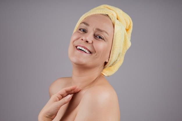 裸の肩を持つ笑う成熟した女性は、灰色の壁のプロファイルで、彼女の肌にクリームを適用します。フェイシャルスキンケアのコンセプト。
