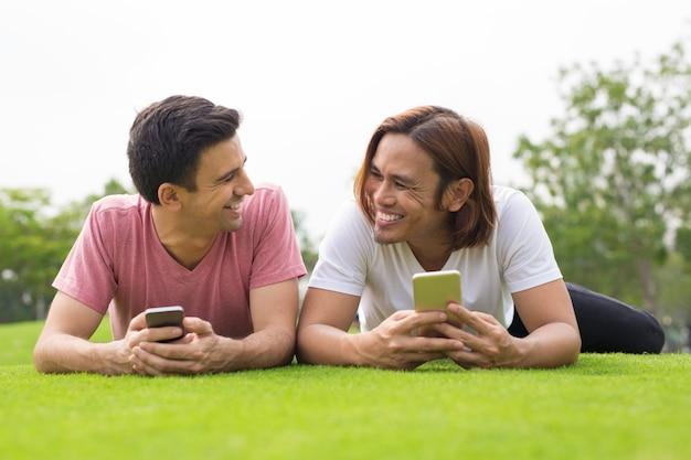 스마트 폰을 사용하고 잔디에 누워 웃는 남자