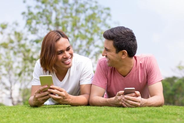 스마트 폰을 사용하고 잔디밭에 누워있는 남자 웃음
