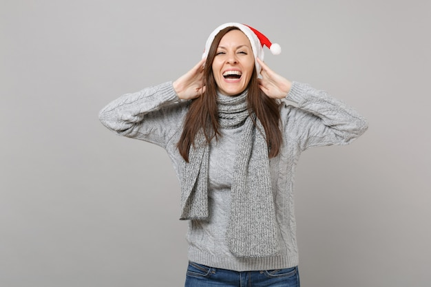 Laughing merry santa girl in gray sweater scarf christmas hat put hands on head isolated on grey background, studio portrait. happy new year 2019 celebration holiday party concept. mock up copy space.