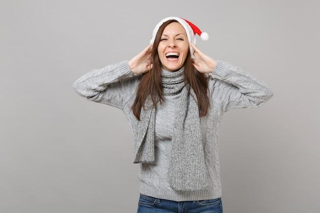 灰色のセーターのスカーフのクリスマスの帽子でメリーサンタの女の子を笑って灰色の背景、スタジオの肖像画に分離された頭に手を置きます。明けましておめでとうございます2019お祝いホリデーパーティーのコンセプト。コピースペースをモックアップします。