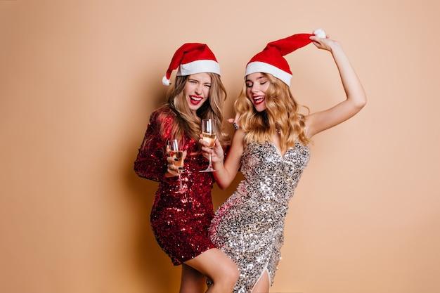 Смеющаяся веселая женщина в красном платье танцует на новогодней вечеринке с другом