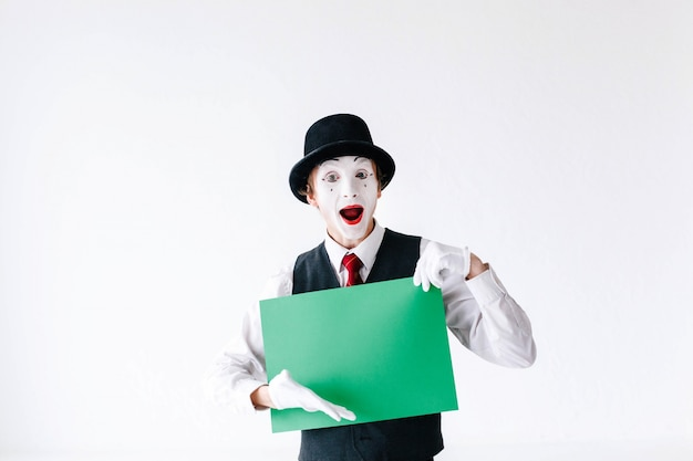 Laughing mime shows something on the green card