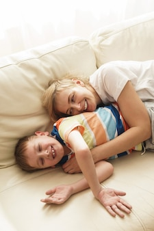 Смеющаяся мать и сын отдыхают на диване в солнечные выходные