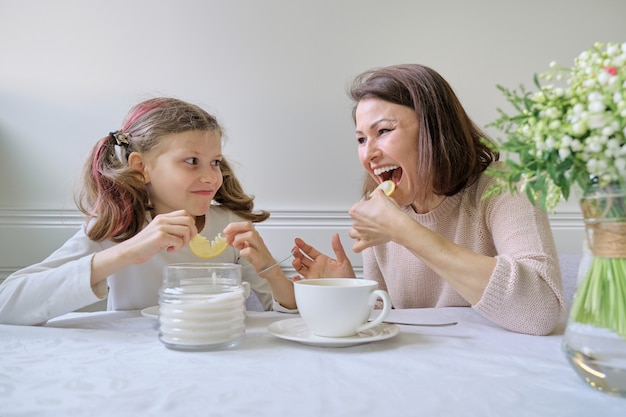 Laughing mother and daughter drinking from cups and eating lemon