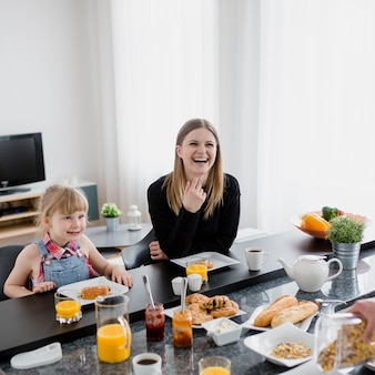 Laughing mother and daughter having breakfast Free Photo