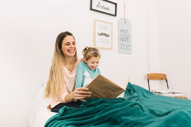 Laughing mother and daughter reading under blanket