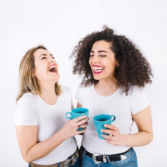 Laughing mother and daughter with mugs