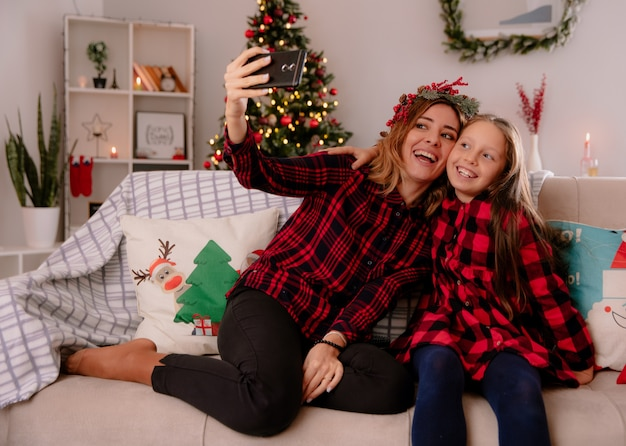 Madre di risata con ghirlanda di agrifoglio e figlia guarda il telefono prendendo selfie seduto sul divano e godersi il periodo natalizio a casa