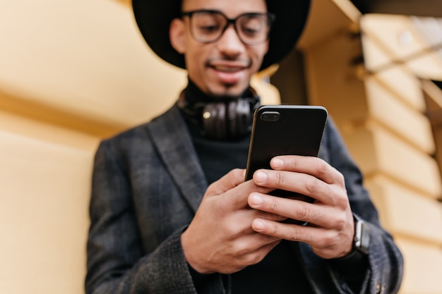 Ridere il messaggio di sms di uomo mulatto sulla strada urbana. ritratto di sfocatura all'aperto del ragazzo sorridente africano con il telefono a fuoco.