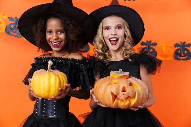 Laughing multinational womans in black halloween costumes holding pumpkins isolated over orange wall