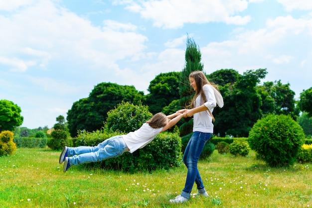 Смеющаяся мама катится на спине маленького сына в парке