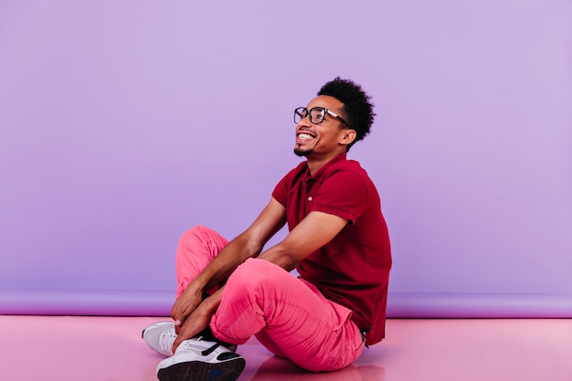 ピンクのズボンに座って楽観的な男を笑う。幸せな笑顔で床にポーズをとる感情的な黒人の若い男。