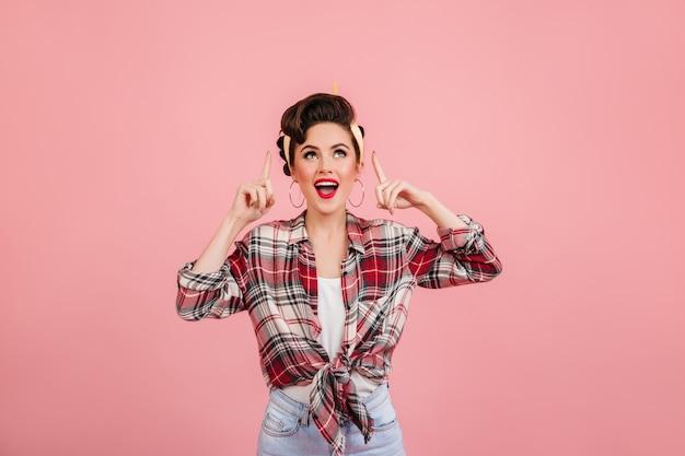 Ragazza di risata del pinup che osserva in su. studio shot di emotiva giovane donna in camicia a scacchi.