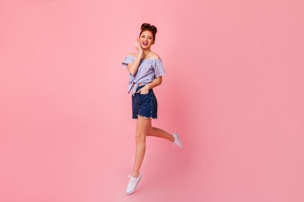 ポケットに手を入れてポーズをとって笑うピンナップガール。ピンクのスペースにジャンプするデニムのショートパンツでかわいい生姜の女性の完全な長さのビュー。