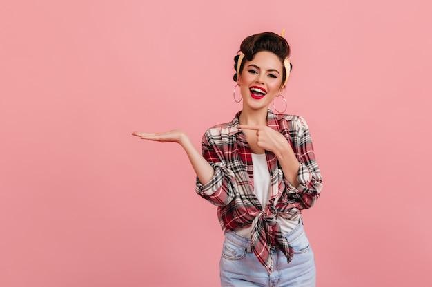 Ragazza pinup di risata che propone con la mano in su. studio shot di moda donna caucasica isolata su sfondo rosa.