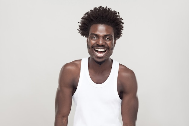 Laughing and positive concept. man looking at camera and smiling. studio shot. gray background