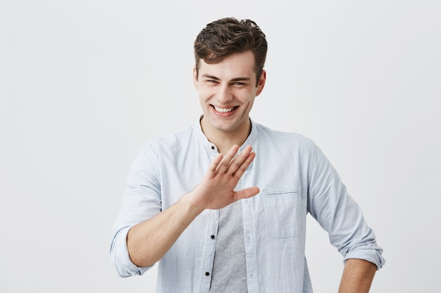 Laughing positive good-looking guy dressed in blue shirt over t-shirt showing stop gesture, asking to stop joking, as he is tired of laughing. young man with stylish haircut smiling