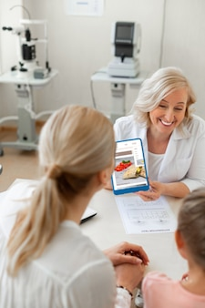 Laughing positive ophthalmologist turning tablet screen to her patient