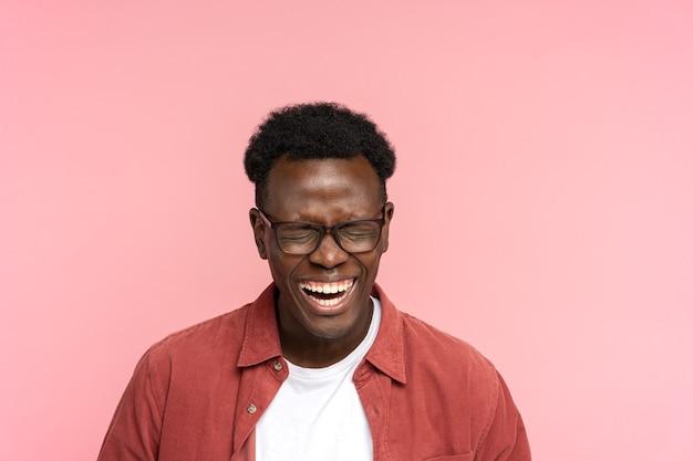 目を閉じて、孤立した良い気分で赤いシャツを着て前向きな若いアフリカ系アメリカ人の男を笑っています。