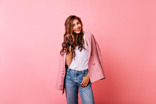 ポジティブな感情を表現するピンクのジャケットでかわいい女の子を笑う。光で隔離の魅力的な生姜の女性の肖像画。