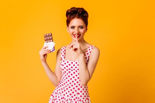 チョコレートを保持している水玉模様のドレスでかわいい女性を笑っています。黄色い空間でポーズをとる至福のピンナップガールのスタジオショット。