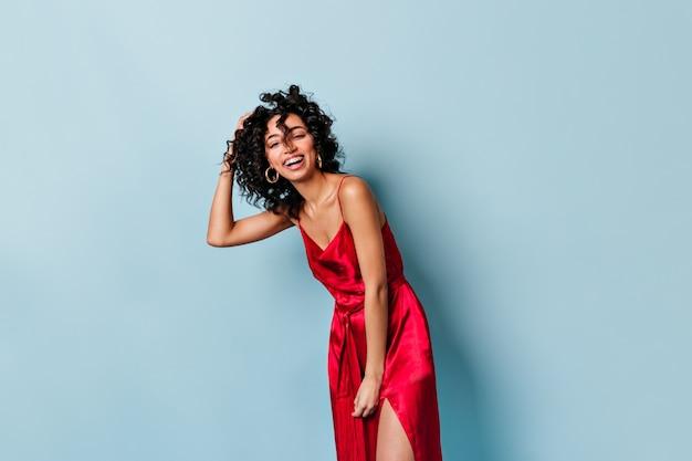 빨간 드레스를 입고 포즈를 취하는 예쁜 여자를 웃 고