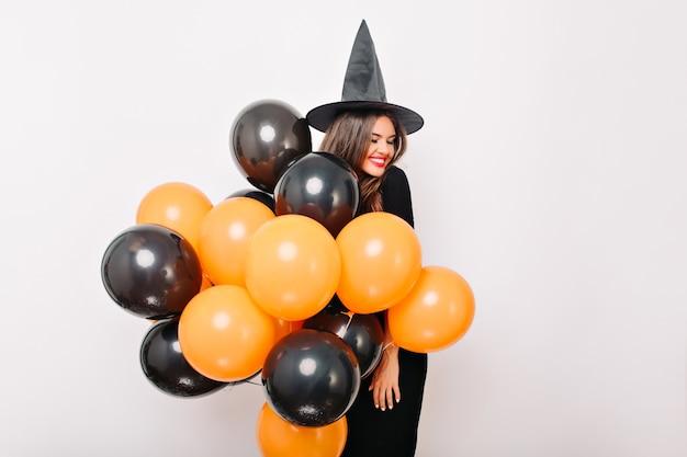 Смеющаяся красивая женщина позирует с кучей воздушных шаров