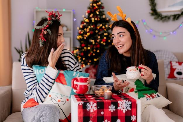 Ragazze carine che ridono tengono le tazze e si guardano seduti sulle poltrone e si godono il periodo natalizio a casa